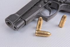 Bullets and gun on aluminium background Stock Photos