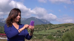 Young girl sliding smartphone in nature outside wired people tourists guide 4K Stock Footage