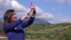 Modern woman taking selfie photo with smart phone in nature wearing blue sweater Stock Footage