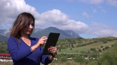 Beautiful girl sliding big tablet in nature outdoors tourist female trip advice  Stock Footage