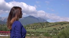 Side view of young girl outdoor admiring mountain landscape relax time in nature Stock Footage