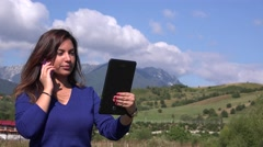 Vacation mood woman in nature talking on mobile phone reading detail from tablet Stock Footage