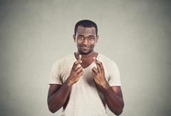Hopeful man crossing fingers isolated grey wall background Stock Photos