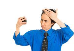Man looking in mirror feeling head surprised shocked he is losing hair Stock Photos