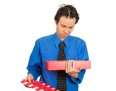 Grumpy man opening gift box looking upset displeased at what he received Stock Photos