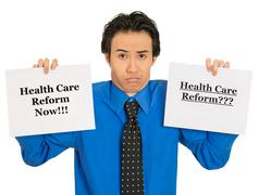 Confused business man holding healthcare reform sign puzzled Stock Photos