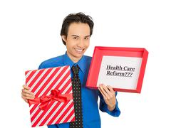 man holding sign health care reform in gift box - stock photo