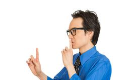 Man placing finger on lips pointing to say shhh be quiet Stock Photos