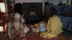4k Shot in Warm and Cozy Atmosphere of a Woman with her Son looking at Fireplace Stock Footage
