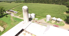 4K Aerial of a silo and corn field on a farm, flying forwards, tilt down Stock Footage