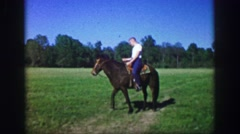 1969: Young man riding horse in open green field showboat equestrian skills. Stock Footage
