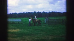 1969: Man helping friend mounting horses riding across farm yard to barn. AMES, Stock Footage