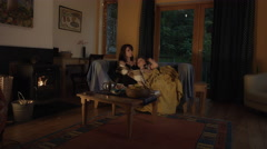 4k Shot in Warm and Cozy Atmosphere of Mom with Son relaxing near Fireplace Stock Footage