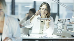 4K Electronics engineers working in lab with woman building circuit board Stock Footage