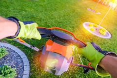Backyard Grass Mowing From Gardener Perspective. Garden Works. - stock photo