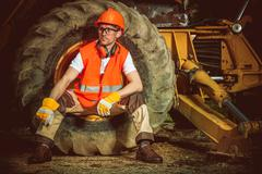 Caucasian Construction Worker While Seating Inside Large Dozer Wheel. Stock Photos