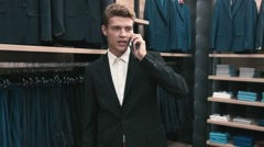 A man in a classic suit talking on a cell phone in shop Stock Footage