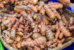 Tumeric rhizomes at the farmers market Stock Photos