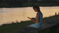 Woman reads electronic book at sunset on the bench Stock Footage