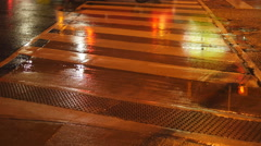 Crosswalk lines painted on road with traffic. Rainy, summer night. Stock Footage