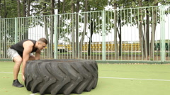 A man picks up a large tire on the Playground. Stock Footage