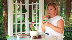 Blonde woman with smartphone relaxing at the summer cafe Stock Footage