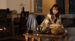 4k Shot in Warm and Cozy Atmosphere of a Woman drinking tea near Fireplace Stock Footage