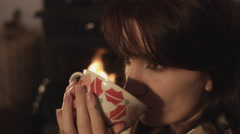 4k Shot in Warm and Cozy Atmosphere - Girl drinking Tea near Fireplace Stock Footage