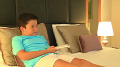 Child lying on a bed and watching cartoon in the bedroom Stock Footage
