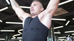 Handsome sporty man is exercising in gym centre Stock Footage