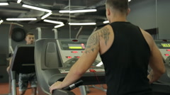 Young athletic men and women exercising and running on treadmill in sport gym. - stock footage