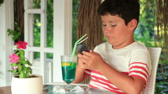 Cute child using smartphone at the summer cafe 3 Stock Footage