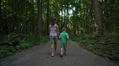 Children holding hands and walking down trail in woods away from camera Stock Footage