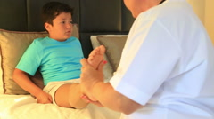 Doctor bandaging her little patient ankle 3 Stock Footage