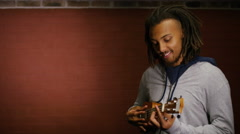 Handsome man with dreads plays a ukulele, in slow motion Stock Footage