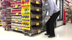Worker exhibiting coffee for sale inside London drugs store Stock Footage