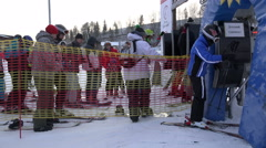 athletes in ski suits and snowboard pass through the turnstile at the T-bar lift - stock footage