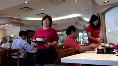 Waitress bringing menu for customer inside Hon's Chinese restaurant Stock Footage
