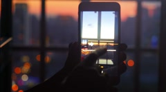 Woman makes a picture from the window with his mobile phone. Night light bokeh Stock Footage