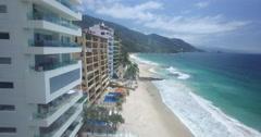 Aerial past beachside properties in Puerto Vallarta Stock Footage