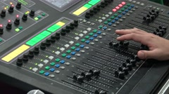 4k An audio engineer adjusts a mixer while a band play in a concert-Dan Stock Footage