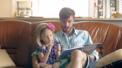 A young father and his happy little blond daughter are reading a story on Stock Footage