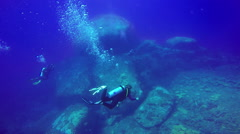 Underwater shot of group scuba divers swimming in a blue clear water. Stock Footage