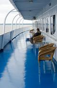 Woman reads newspaper on deck of river cruise ship Stock Photos