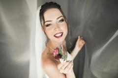 Beautiful young bride with makeup and hairstyle in bedroom, newlywed woman final - stock photo