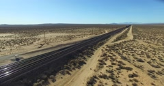 A dramatic aerial over a freight train as it travels at a high speed across a Stock Footage
