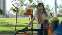 Teens ride on the swings at the playground. defocused Stock Footage