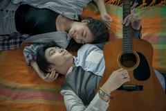 Couples of asian younger man and woman playing guitar with relaxing and happi Stock Photos