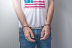 Arrested man with cuffed hands wearing shirt with USA flag Stock Photos