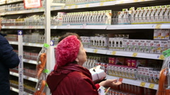SuperMarket, women choose products on the shelves Stock Footage